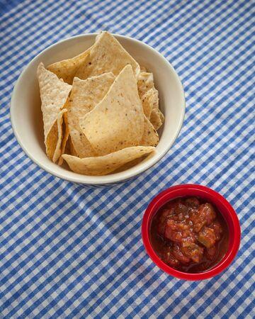 tortilla de maiz: Un tazón de chips de tortilla de maíz se sienta al lado de un recipiente de color rojo de la salsa en un mantel azul y blanco a cuadros