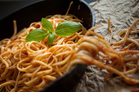 crinkled: Linguine with red sauce and fresh basil sits inside a black cast iron pan on a crinkled brown paper surface.