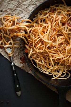 Linguine with red sauce sits inside a black cast iron pan on a black surface.  A fork sits beside the pan. Reklamní fotografie