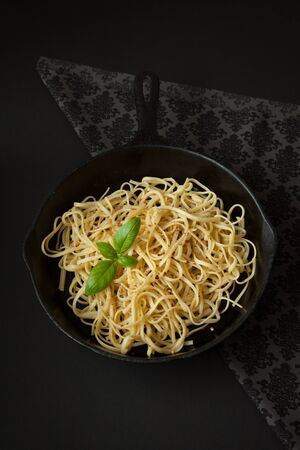 Linguine sits inside a black cast iron pan on a black surface.  A sprig of basil sits atop the pasta. Imagens