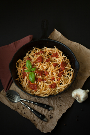 cast off: Linguine with red sauce and a sprig of basil sit inside a black cast iron pan on top of a brown paper bag surface.  A napkin, fork, and spoon are in the frame. A bulb or garlic sits off to the side. Stock Photo