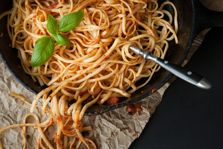 cast iron red: Linguine with red sauce  and fresh basil sits inside a black cast iron pan on a black surface.  A fork sticks out of the pasta. Stock Photo