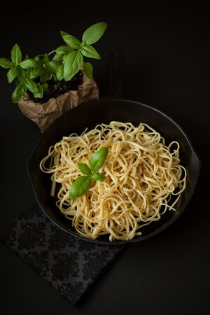 Linguine sits inside a black cast iron pan on a black surface.  A sprig of basil sits atop the pasta.  A basil plant is in the background. Reklamní fotografie