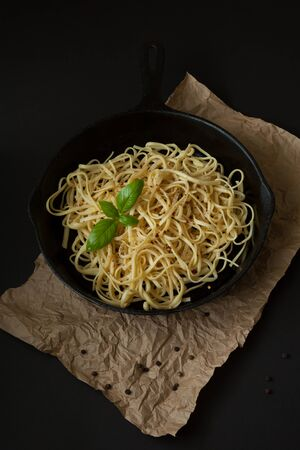 Linguine sits inside a black cast iron pan on a black surface with a crumpled brown paper bag beneath.  A sprig of basil sits atop the pasta.