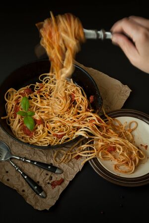 plating: Linguine with red sauce and a sprig of basil sit inside a black cast iron pan on top of a brown paper bag surface.  A napkin, fork, and spoon are in the frame. The motion of a hand with a fork can be seen plating the pasta.