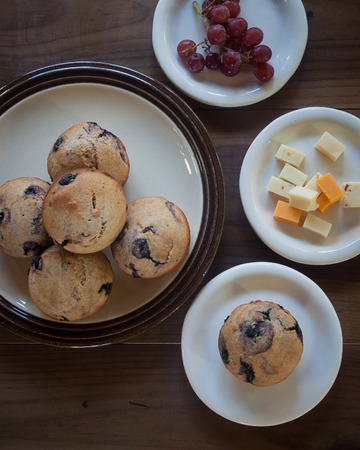 seedless: Several plates containing blueberry muffins, cheese cubes, and red seedless grapes sit on a brown wooden tabletop.