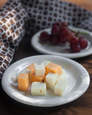 dappled: A white plate of various cubed cheeses  sits atop a brown wooden tabletop.  A white plate of red seedless grapes on the vine is seen in the background.  Dappled  light from the trees outside is shadowed and reflected in the scene.