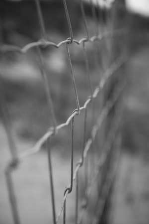 suspense: Black and white image of wire fence; vertical image