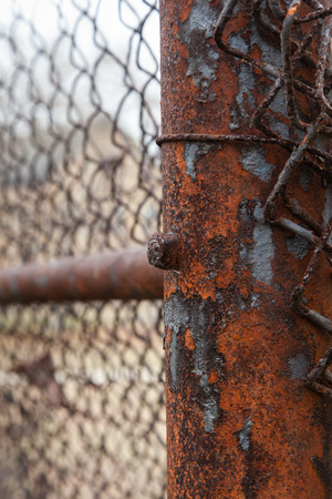 Rusty iron on old chain link fence post; vertical image Stock Photo