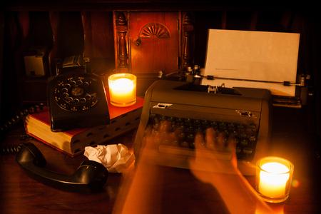 Ghost handen op uitstekende schrijfmachine; vintage roterende telefoon naar links zittend op een oud boek; afbeelding wordt verlicht door kaarslicht