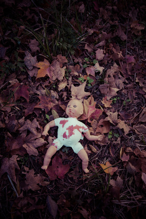 Abandoned baby doll in woods Stock Photo