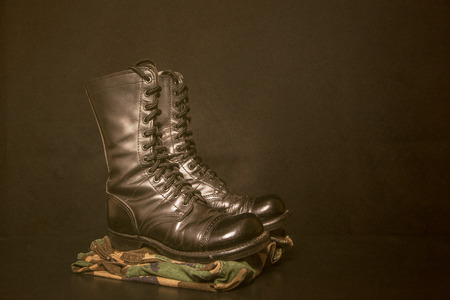 army boots: A pair of combat boots with camouflage fatique pants on a black, vintage styled  background.