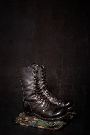 combat boots: A pair of combat boots with camouflage fatique pants on a black background.