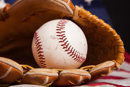A baseball and glove with an American flag background. 免版税图像
