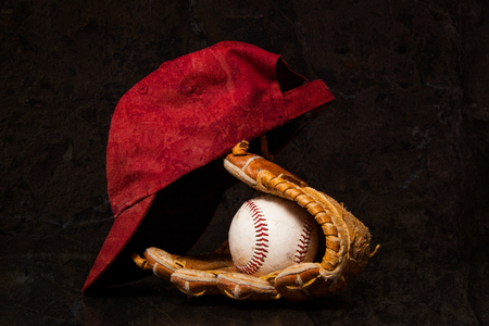 red gloves: A baseball and glove with a baseball cap on a black background. Stock Photo