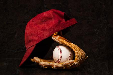 ?  ?      ?  ?     ?  ?    ?  ? gloves: Un guante de béisbol y con una gorra de béisbol sobre un fondo negro.