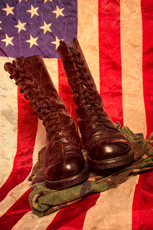fatigues: A pair of combat foots and camouflage pants with an American Flag. Stock Photo
