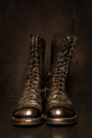 combat boots: A pair of combat boots with a black background and textured feel.