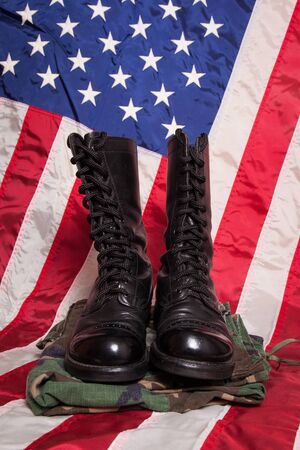 us soldier: A pair of combat foots and camouflage pants with an American Flag. Stock Photo
