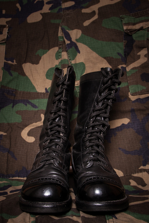 fatigues: A pair of combat boots on a camouflage background.