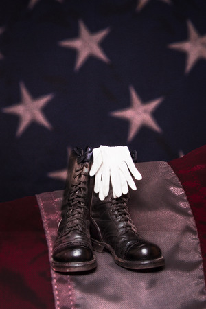 combat boots: A pair of combat boots and white dress gloves on an American Flag background. Stock Photo