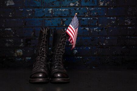 estrellas  de militares: Un par de botas de combate con una pequeña bandera estadounidense sobre un fondo de ladrillo azul. Foto de archivo