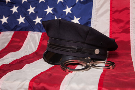 A police hat with handcuffs on an American flag background.