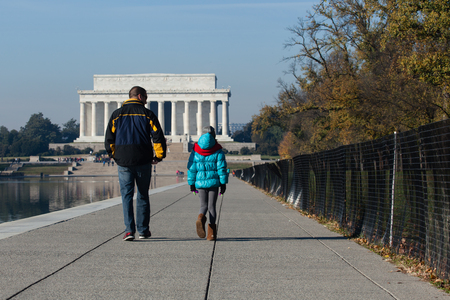 lincoln memorial: Washington DC - December 6, 2015:  A man and child seen walking along the reflection pool headed toward the Lincoln Memorial