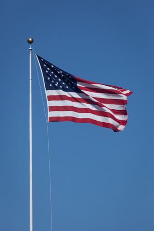 breeze: An American Flag waves in the breeze against a crisp blue sky.