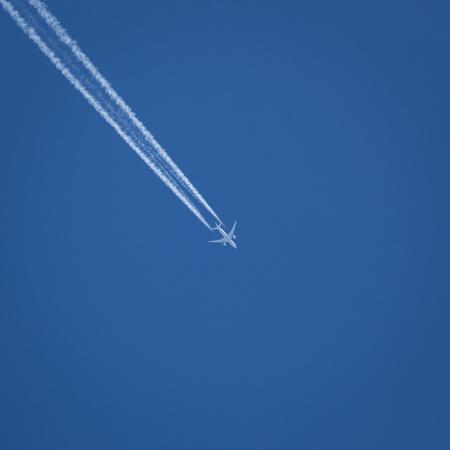 A commercial jet flies against a crisp blue sky.