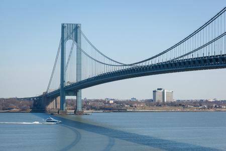staten: STATEN ISLAND, NEW YORK - MARCH 1: The Sea Streak Ferry goes under the Verrazano-Narrows Bridge on March 1, 2016.