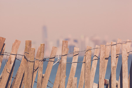 staten: The Manhattan skyline, as seen from Fort Wadsworth in Staten Island.  The skyline is blurred behind the fence.