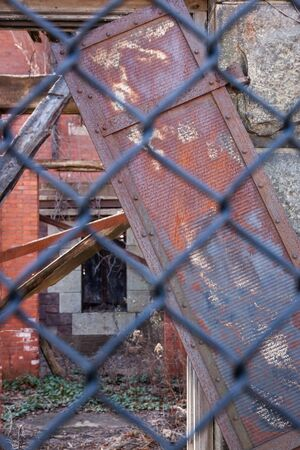 voyeur: Details of architectural decay seen through a chain link fence.