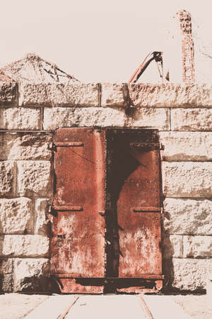 suspense: An old iron door is rusted out at an old military fort.