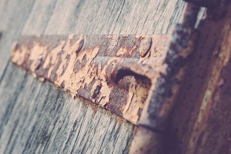 suspense: Details of an old rusty hinge on wooden shutters. Stock Photo