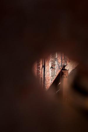 suspenso: Un pequeño orificio proporciona un espacio para mirar a través de una vieja abandonada en la estructura,, militar en decadencia.