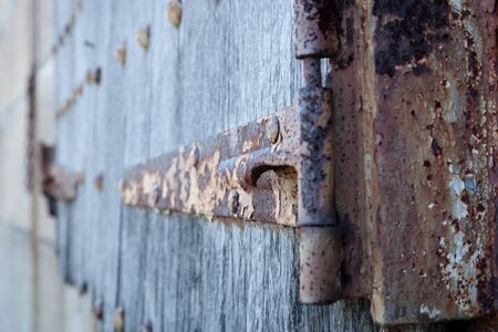 suspenso: Detalles de un viejo bisagra oxidada en persianas de madera.