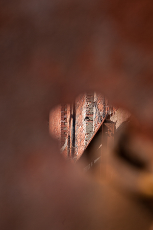 voyeur: A small hole provides a space to peek through into an old, abandoned, military structure in decay.