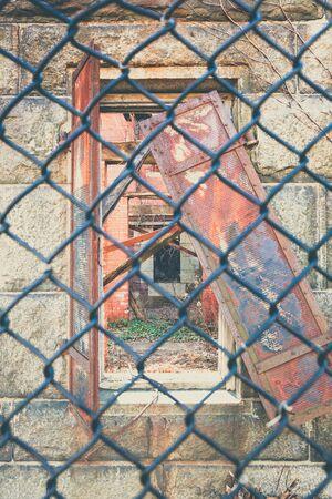 suspenso: Detalles de la decadencia arquitect�nica vistos a trav�s de una valla de tela met�lica.