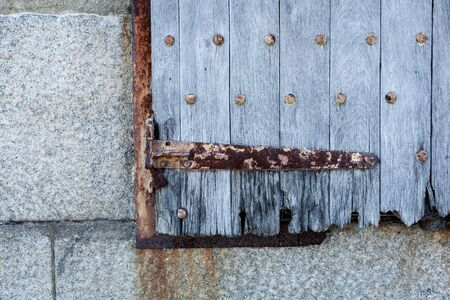 suspense: A closeup of an old wooden shutter with rusty metal accents. Stock Photo