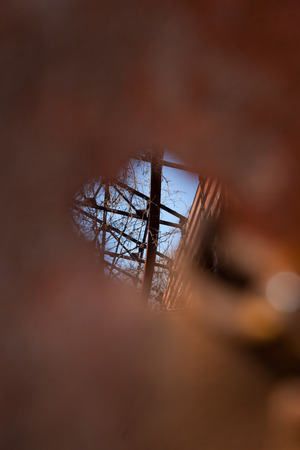 peek: A small hole provides a space to peek through into an old, abandoned, military structure in decay.
