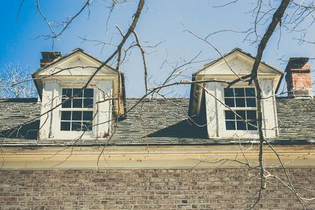 suspenso: Las viejas ventanas son vistos a través de ramas de los árboles estériles.