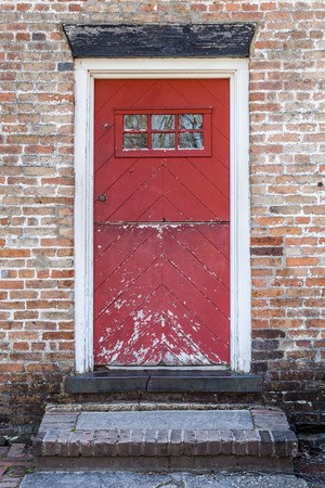 suspense: An old red door is closed on a brick building. The paint is peeling and in decay.