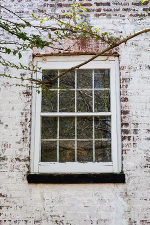suspenso: Una ventana con paneles de vidrio en un blanco lavó casa de ladrillo. Una rama de árbol enmarca la foto. Foto de archivo