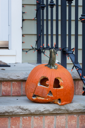 A moldy, decaying jack-o-lantern sits on someones front steps after Halloween. Stock Photo