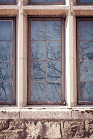 commision: Windows on a tudor style house. The reflection of winter trees can be seen. This structure is part of the Palisades Interstate Park Commission building in Alpine, New Jersey.