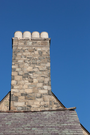 commision: An old stone chimney is visable on a tudor style house. This structure is part of the Palisades Interstate Park Commission building in Alpine, New Jersey.