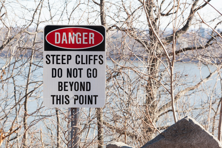 steep cliff sign: A sign warns people to not go beyond this point at the cliffs of the Palisades Interstate Parkway in Alpine, New Jersey. Stock Photo