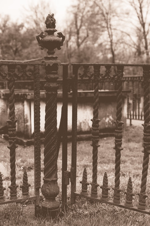 appears: An old weathered crypt sits inside a metal fenced in area in a cemetery. The top appears to have shifted. Stock Photo