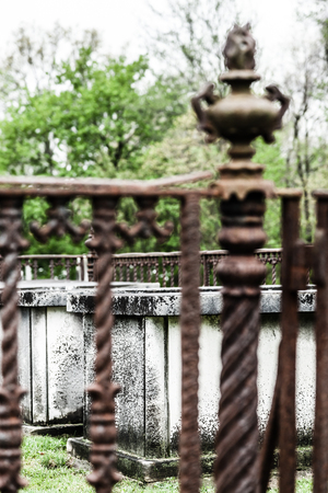 An old weathered crypt sits inside a metal fenced in area in a cemetery. The top appears to have shifted. Stock Photo
